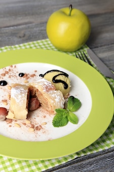Вкусный домашний яблочный штрудель с орехами, листьями мяты и мороженым на тарелке, на деревянном фоне