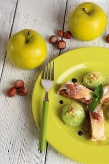 Вкусный домашний яблочный штрудель с орехами, листьями мяты и мороженым на тарелке, на деревянной поверхности