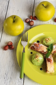 Tasty homemade apple strudel with nuts, mint leaves and ice-cream on plate, on wooden surface