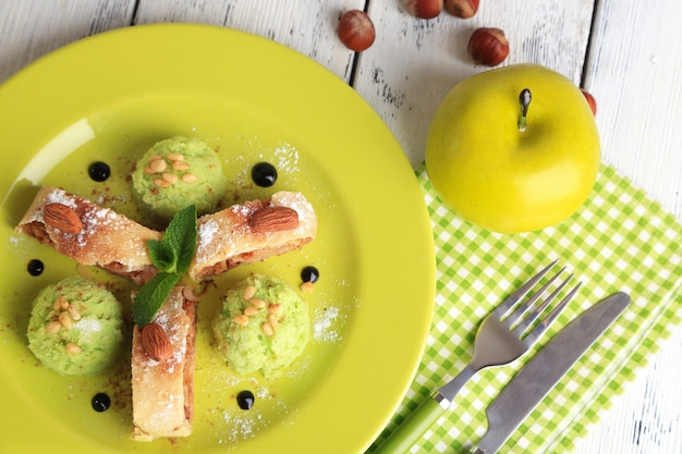 Tasty homemade apple strudel with nuts, mint leaves and ice-cream on plate