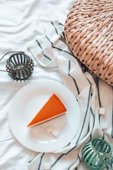 部屋のベッドの白い皿にキャラメルを添えたおいしい自家製キャラメルチーズケーキ。