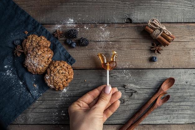 木製のテーブルの上に横たわっているスパイススプーンと巻き毛のキャンディーとおいしい自家製クッキー