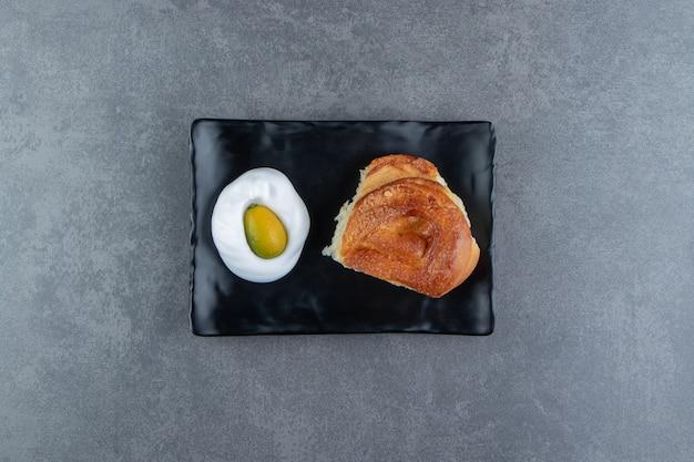 黒いプレートにおいしい自家製の新鮮なパン。