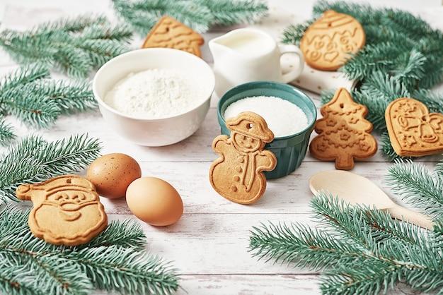 Вкусное домашнее имбирное печенье. ингредиенты для выпечки, посуда, пряники. открытка с новым годом. рождественский стол. ель, сосна.