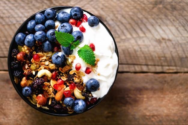 Tasty homemade granola, yogurt, fresh organic berries, pomegranate, mint on rustic wooden
