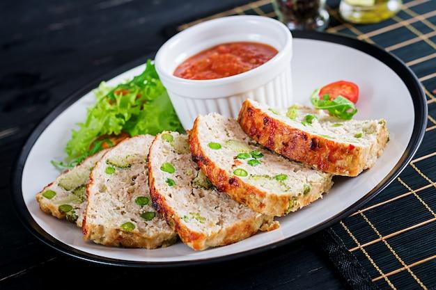 Вкусный домашний запеченный куриный рулет с зеленым горошком и брокколи на черном столе. еда американского мясного хлеба.