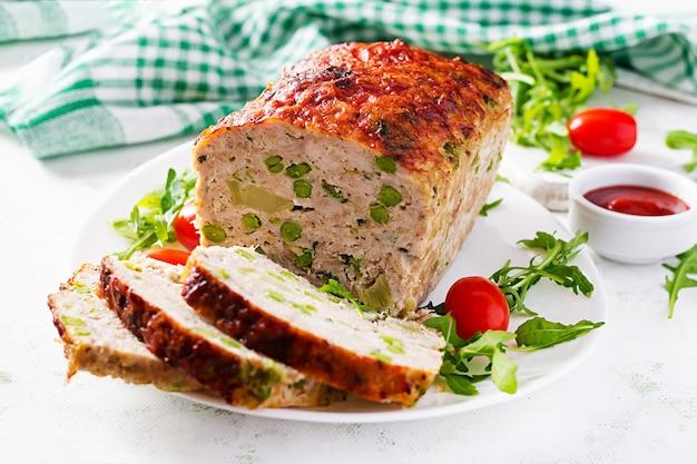 Вкусный домашний фарш из куриного мясного рулета с зеленым горошком и нарезанной брокколи на белом столе