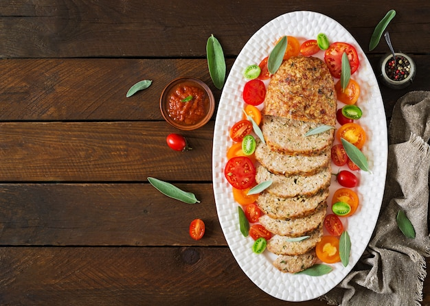 Tasty homemade ground  baked turkey meatloaf in white plate on wooden table