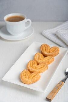 Вкусное домашнее печенье в форме сердца в форме сердца, лежащее на тарелке, подается с чашкой черного кофе
