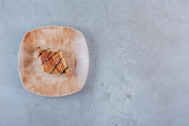 На тарелке выложена вкусная домашняя выпечка, украшенная шоколадом.