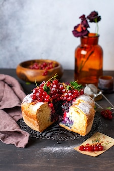 Вкусный домашний пирог с красной смородиной и свежей красной смородиной на темно-сером деревенском фоне. летний пирог или выпечка.