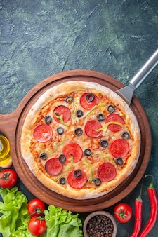 木の板の上のおいしい自家製ピザオイルボトルトマトペッパーグリーンバンドル暗い表面の底に