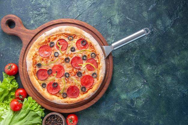 Gustosa pizza fatta in casa sul bordo di legno bottiglia di olio pomodori pepe verde fascio sulla superficie scura