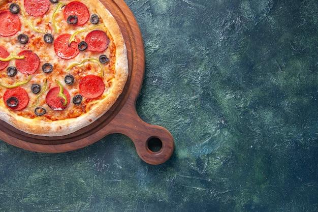 Gustosa pizza fatta in casa su tavola di legno sul lato destro su superficie scura isolata