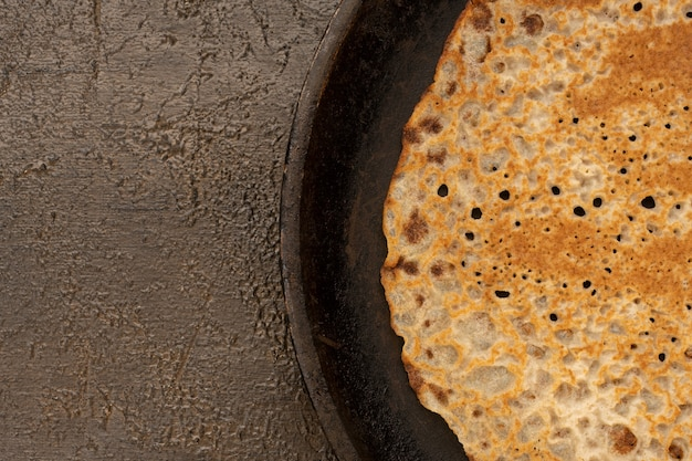 Tasty homemade rustic pancake in a frying pan on wooden table. table top view. maslenitsa food.