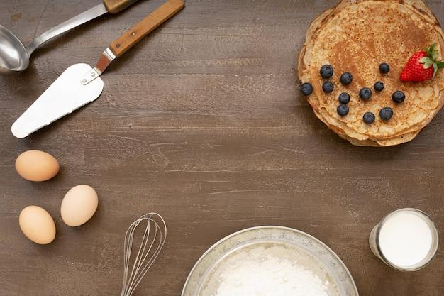 木製のテーブルにベリーとおいしい自家製の素朴なパンケーキ。テーブルトップビュー。マースレニツァ食品。