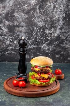 어두운 색상 표면에 나무 커팅 보드에 맛있는 수제 샌드위치 토마토 고추