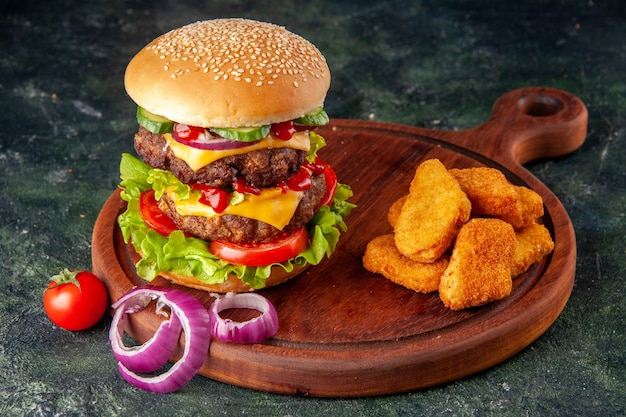 Tasty homemade sandwich tomatoes pepper on wooden board onions tomato with stem chicken nuggets on dark color surface