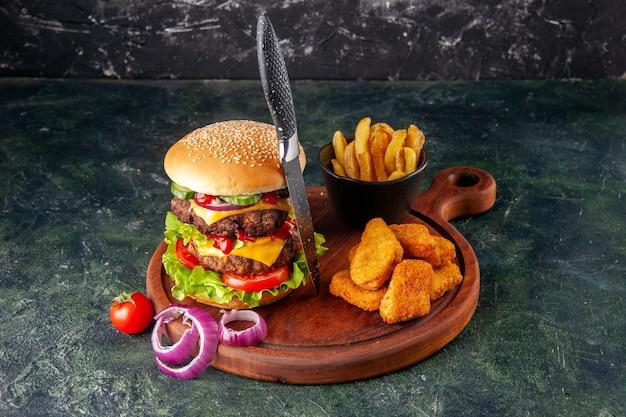 Gustoso panino fatto in casa pomodori pepe sul tagliere di legno cipolle pomodoro con gambo pepite di pollo patatine fritte forcella sulla superficie di colore scuro