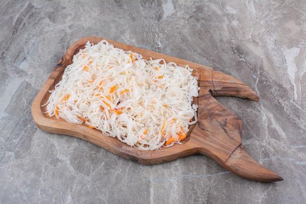 나무 보드에 맛있는 수제 소금에 절인 양배추.