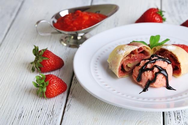 나무 배경에 접시에 아이스크림, 신선한 딸기, 민트 잎을 곁들인 맛있는 홈메이드 슈트루델