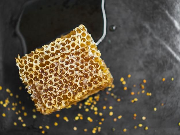Вкусный сотовый кусок и пыльца пчел на черном фоне