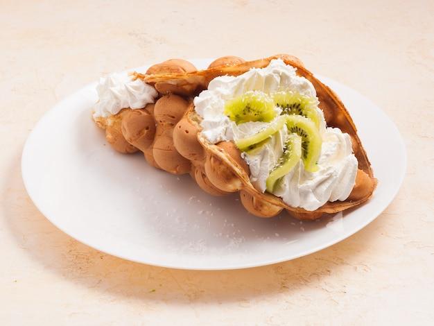 Вкусные гонконгские вафли с киви и взбитыми сливками на белой тарелке