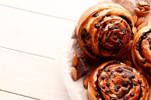 Вкусные горячие булочки с корицей и шоколад на белом деревянном фоне. сладкие булочки с корицей fresh homemade. место для текста. вид сверху.