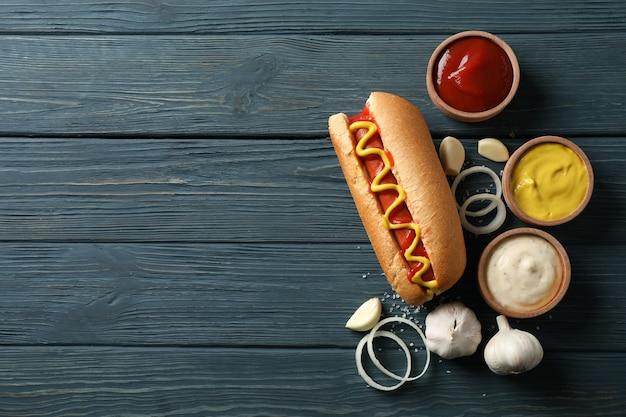 Вкусный хот-дог и ингредиенты на деревянной поверхности