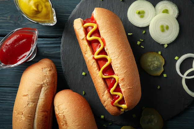 Tasty hot dog and ingredients on wood