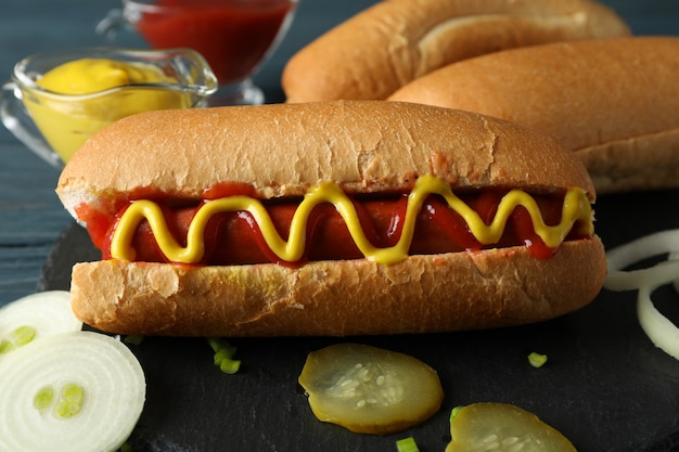 Tasty hot dog and ingredients on wooden surface