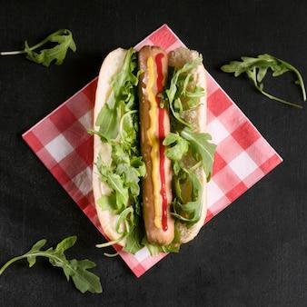 Вкусный хот-дог с овощами на салфетке