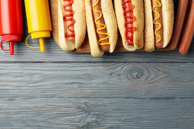 Вкусные хот-доги и соусы на серой деревянной поверхности