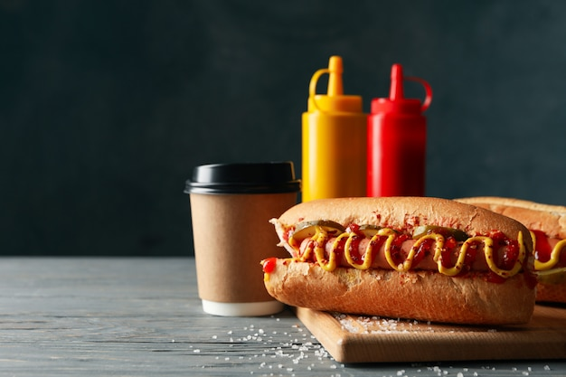Tasty hot dogs, coffee and sauces on wood