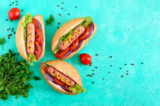 Вкусные хот-доги. жареная колбаса с помидорами, красным луком, листьями салата, горчицей в хрустящей буханке. уличная забегаловка. быстрое питание. вид сверху