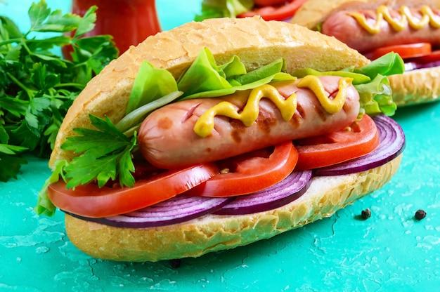 Вкусные хот-доги. жареная колбаса с помидорами, красным луком, листьями салата, горчицей в хрустящей буханке. уличная забегаловка. быстрое питание.