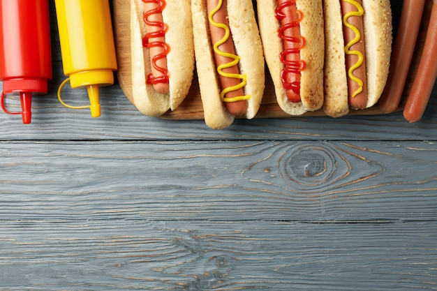 Tasty hot dogs and sauces on gray wooden surface