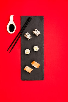 Tasty hot sushi rolls served with soya sauce on slate stone and chopsticks over red background