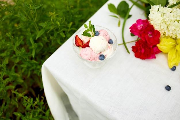 おいしいアイスクリームと新鮮なブルーベリー、ボウルに入ったイチゴ、夏のパーティーで庭のテーブルに花を添える