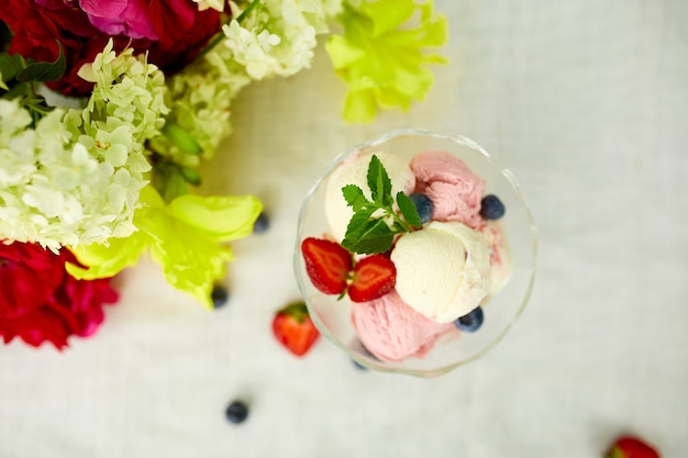 Tasty ice cream and fresh blueberries, strawberry in the bowl, presented with flower on a table in a garden during summer season for a party