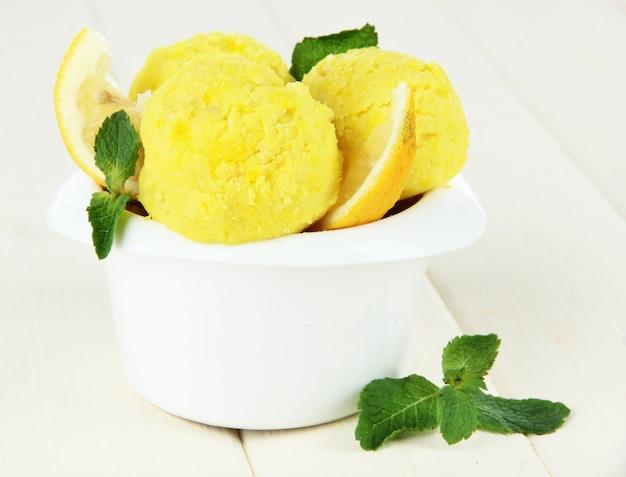 Вкусные шарики мороженого в миске, на деревянном столе