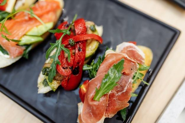 Вкусные итальянские брускеты-закуски с помидорами, анчоусами, прошутто, моцареллой, креветками и морепродуктами.