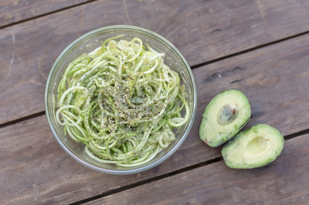 Tasty italian fettuccine pasta cooked with avocado pear, fresh tomato and pine nuts garnished with grated parmesan and serving in a rustic frying pan on an old wooden table