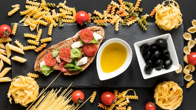 Tasty italian food with uncooked pasta; black olives and bowl of oil over black surface