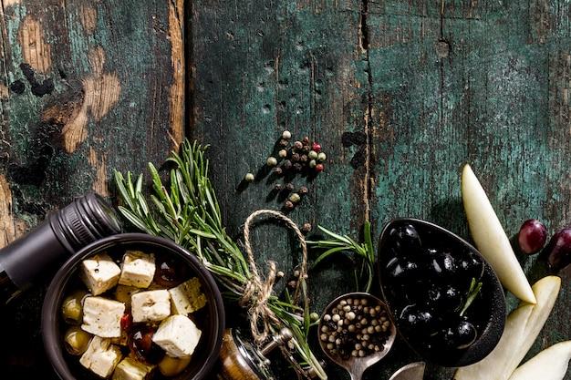 Tasty italian greek mediterranean food ingredients top view on green old rustic table above