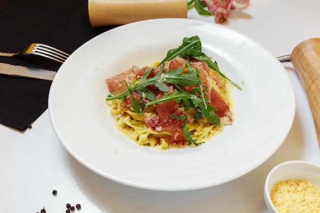 Tasty italian pasta appetizer with basturma and fresh basil on top on a white table background with docures.