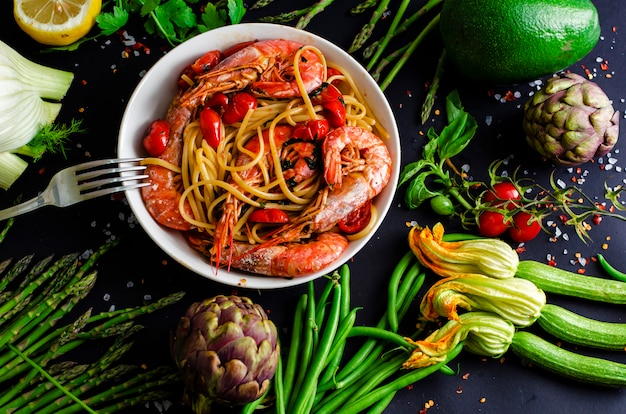 Tasty italian pasta with tiger prawns or shrimps and fresh vegetables on black .