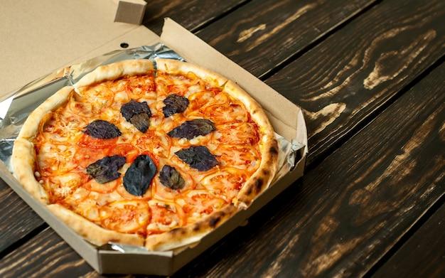 Вкусная итальянская пицца в коробке на фоне дерева с копией пространства для вашего текста