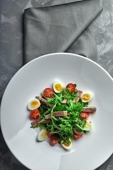 Вкусный итальянский салат из говяжьего языка с яйцами, рукколой, помидорами, специями и соусом