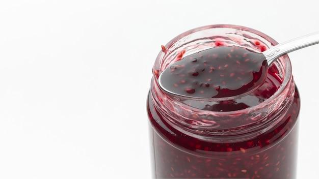 Tasty jam in transparent jar